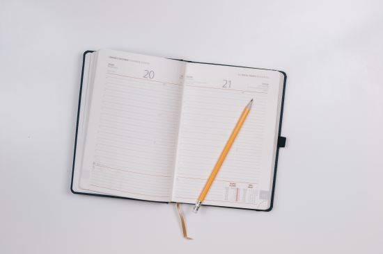 An open diary with a yellow pencil lying across the pages, on a white background