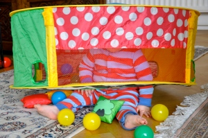 Child with toy on head surrounded by colourful plastic balls.
