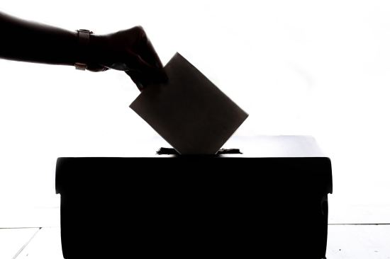 A silhouette of a hand placing a vote into a ballot box