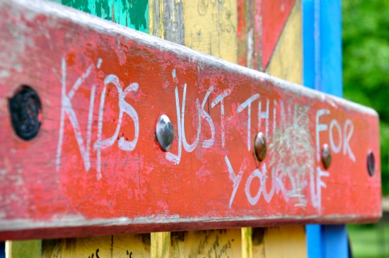 Graffiti in a playground saying Kids Just Think for Yourself