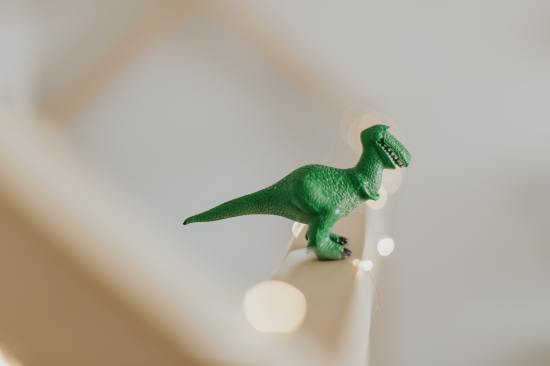 green toy dinosaur on a white stair banister