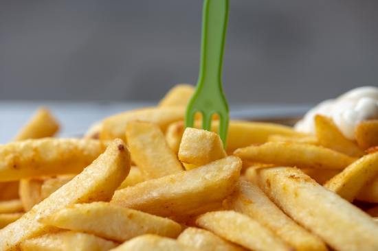 Plate of chips (french fries) with a green plastic fork