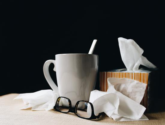 white mug, glasses and box of tissues on a bedside table, implying sickness