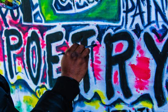 Image of a hand painting the word 'poetry' in bright colours on a graffiti wall.