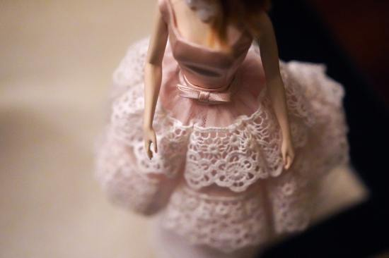 Close up image of a female doll wearing a pink dress