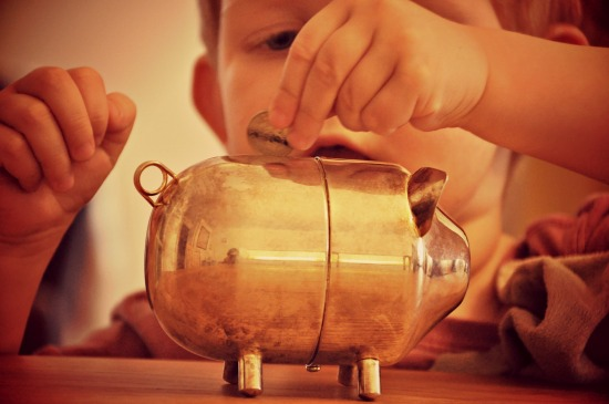 child putting coins in piggy bank