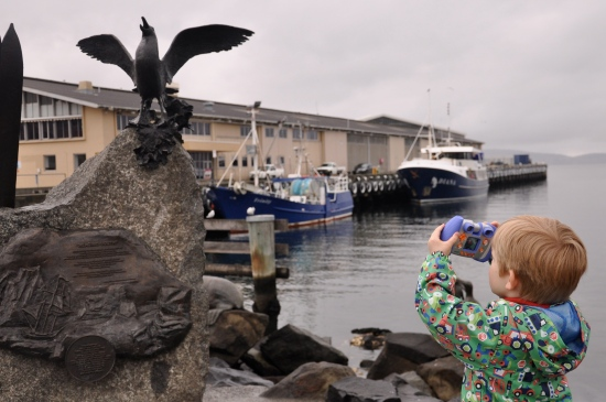 A young boy taking a photo of a statue at Hobart waterfront in Tasmania