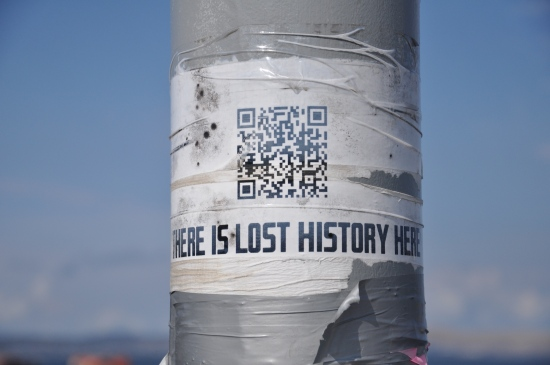 An image of a QR code on a lamppost at Hobart Waterfront in Tasmania, which says 'There is lost history here'.