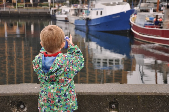 A young boy taking photos of the boats at Hobart waterfront