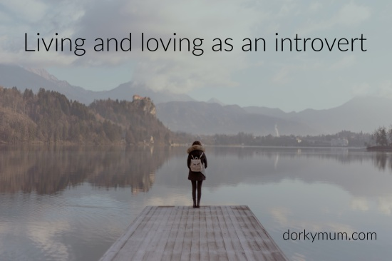 A woman standing along overlooking a lake, with the text 'living and loving as an introvert'