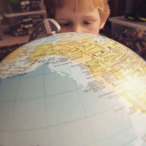 Young boy looking at globe