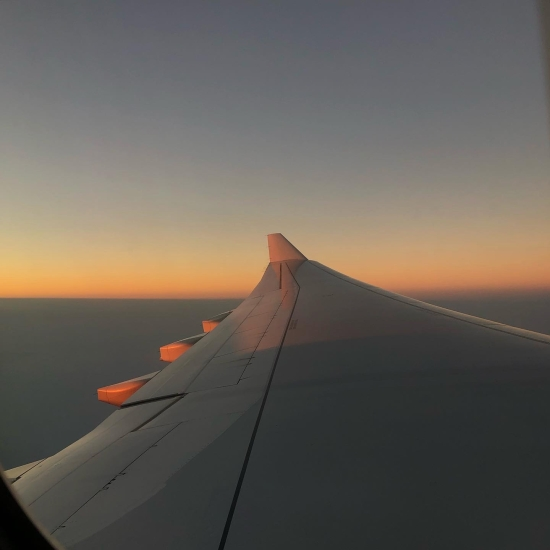 A view looking along an Aeroplane wing - above the clouds and flying to Hawaii