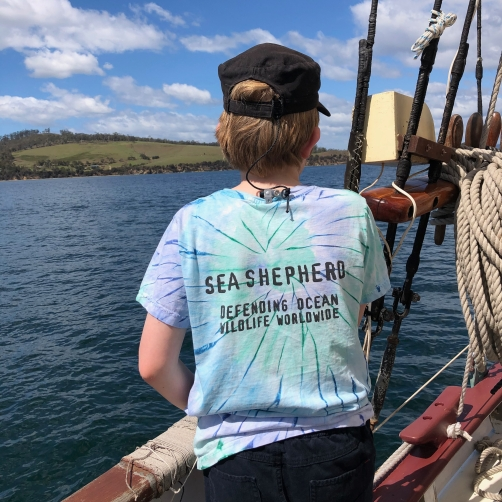 Boy in Sea Shepherd tshirt standing onboard the SV Rhona H wooden ship near Hobart Tasmania