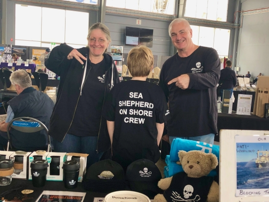 Three people in Sea Shepherd t-shirts standing at a stall selling merchandise