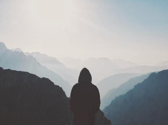 A man alone with his hood up looking out at a valley