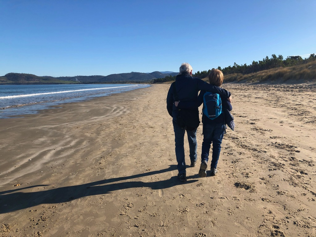 Two figures walking on a beach